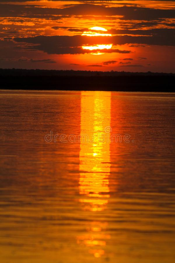 The solar disk falls over the horizon line. Reflection of the sunset on the watery surface stock image