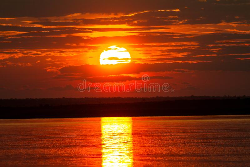 The solar disk falls over the horizon line. Reflection of the sunset on the watery surface stock photo