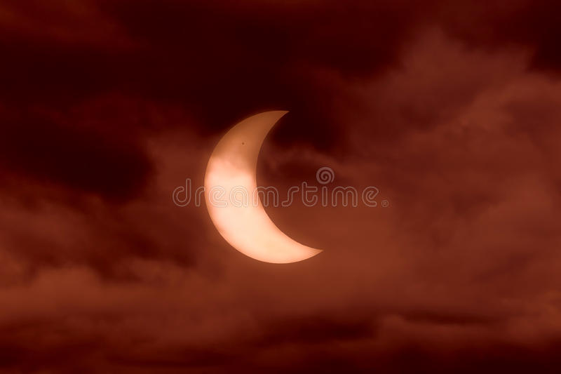 Solar eclipse. Partial solar eclipse on january 4th 2011 visible through clouds. Landscape orientation royalty free stock photo