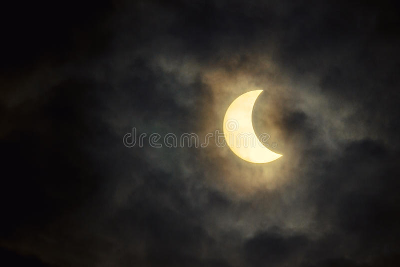 The solar eclipse in the cloudy sky royalty free stock photography
