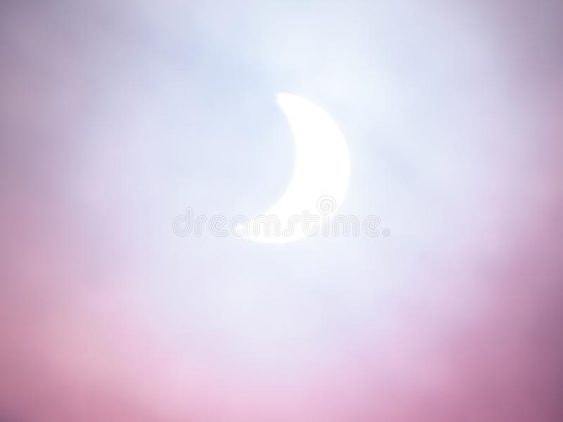 Solar eclipse, soft artistic background. White, blues and pinks. Solar eclipse. The moon passing in front of the sun partly obscuring it. Soft artistic royalty free stock photos