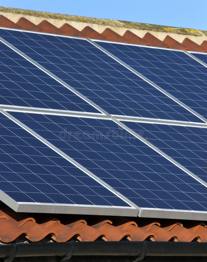 Solar Energy - Domestic Heating. Photovoltaic Solar heating panels on the roof of a house. Hot water heated by the sun on a residential roof to provide domestic royalty free stock photography