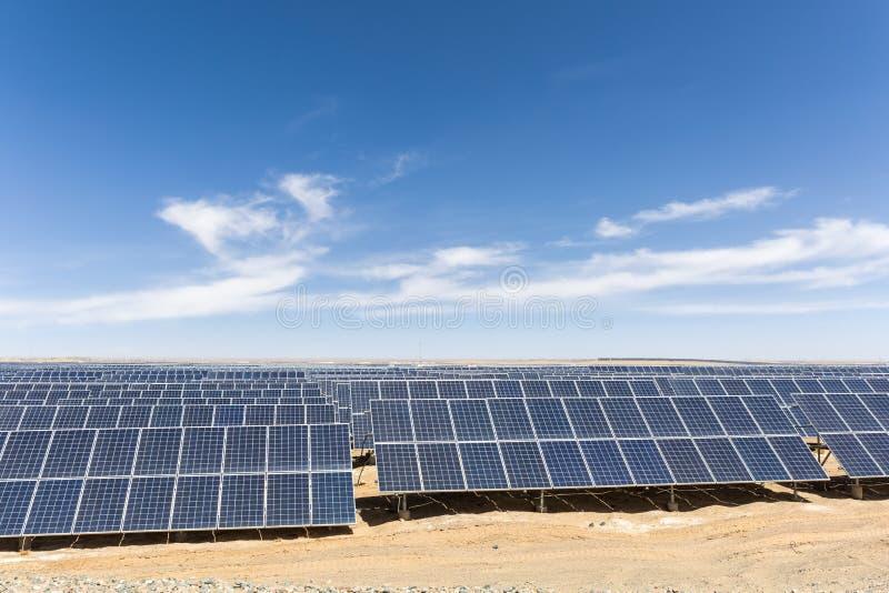 Solar energy on gobi. Solar panels on the gobi against abundant sunshine sky, new energy background stock image