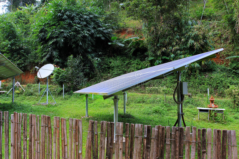 Renewable solar energy and telecommunications in a village of East Asia, in jungle. Solar energy panels telecommunications antenna installed in a village of East royalty free stock photography