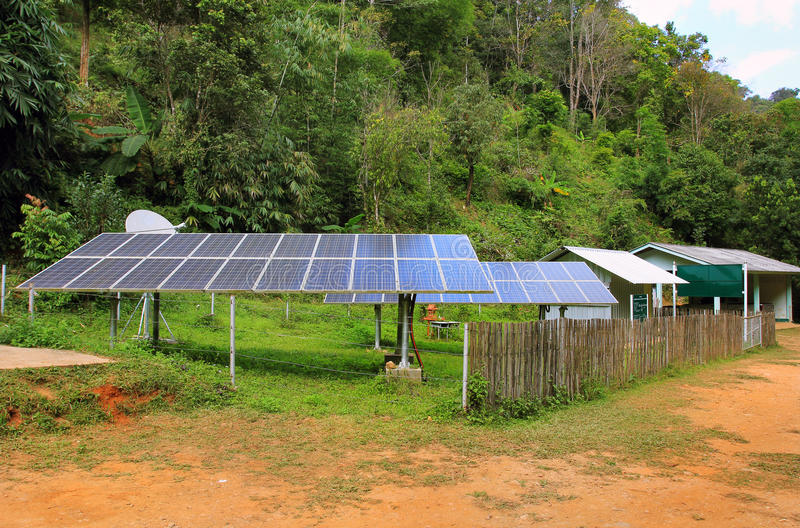 Renewable solar energy in a village of East Asia, in jungle. Solar energy panels installed in a village of East Asia, in the jungle forest in a province. A budda stock photography