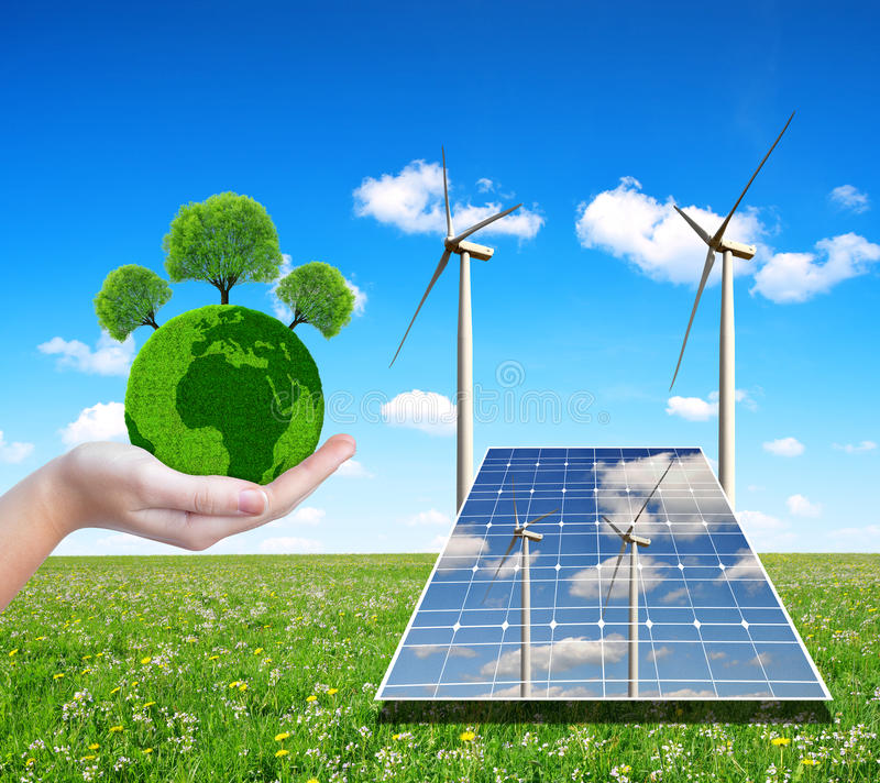 Solar energy panels with wind turbines and green planet in hand. stock photos