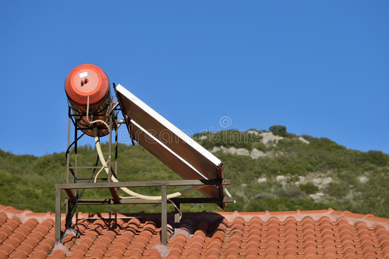 Solar energy sistem. Solar water heater sits on the roof of a home in greek village, Greece royalty free stock photography