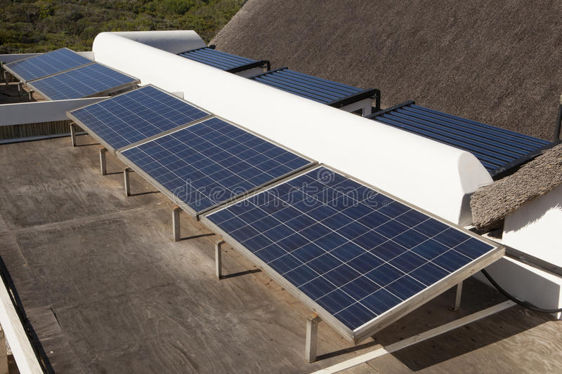 Solar heating. A private installation of photovoltaic panels and solar water heating panels at a residential house stock photography