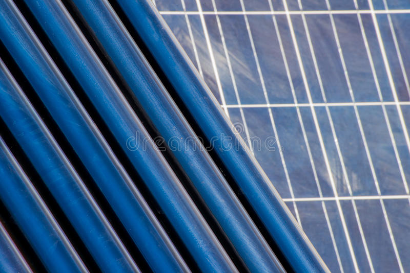 Solar heating tubes in front of a solar panel. Solar heating tubes used for heating water are situated with a solar panel as background stock photography
