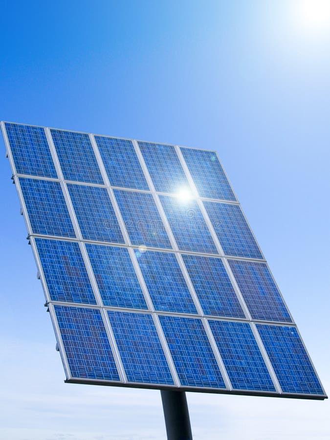 Solar panel. Sun shining in a solar panel against a blue sky royalty free stock photos