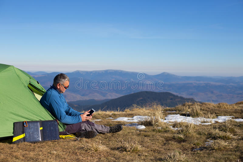 The solar panel attached to the tent. The man sitting next to mobile phone charges from the sun. Solar panel.The solar panel attached to the tent. The man stock photography