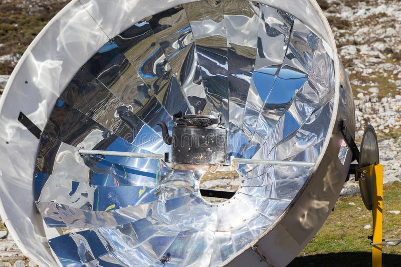 Solar panel cooker in Nepal mountains. Solar panel cooker heating water kettle teapot, renewable green energy source, Nepal mountains. Everest Base Camp route royalty free stock images
