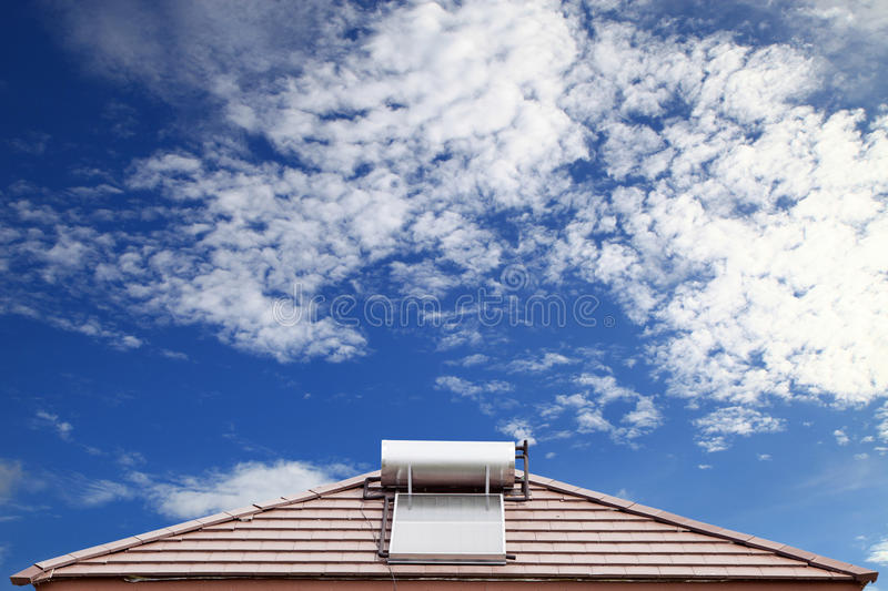 Solar panel for hot water system on roof on blue sky background. Solar panel for hot water system on roof on blue sky background stock photo