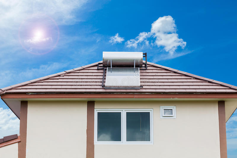 Solar panel for hot water system on roof on blue sky and sun background. stock photo