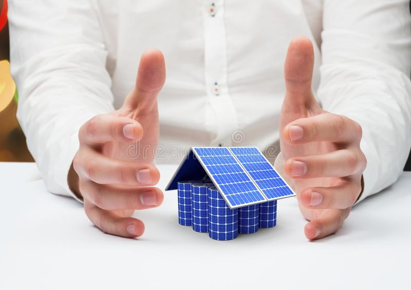 solar panel house between a hands stock photography