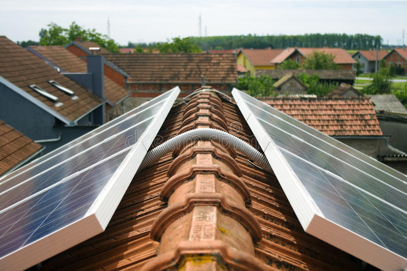 Solar panel on house roof. Detail of cable connecting solar panels on house roof stock image