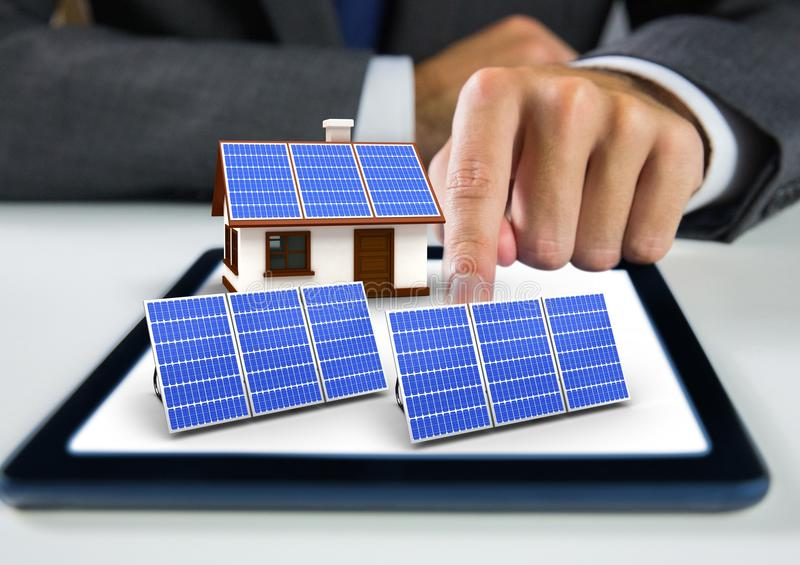 solar panel and house with solar panel on tablet with businessman hand stock images