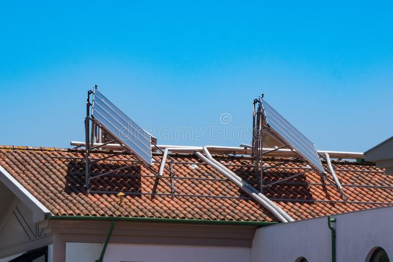 Solar panels on red tiled roof of apartment building royalty free stock photos