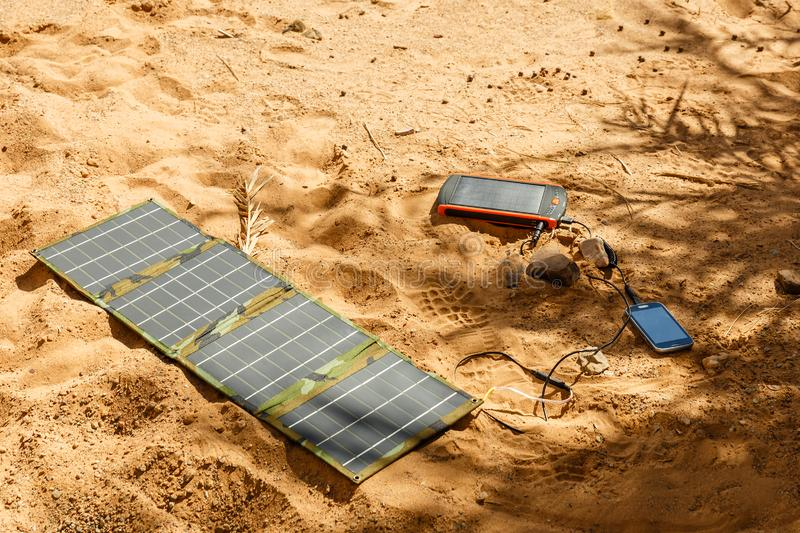 Solar panel lying on the ground and charges the phone. Solar panel lying on the ground and charges the smart phone, the Sahara desert. Charge smart phone from royalty free stock photography