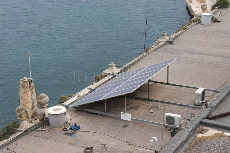 Solar panel on messy rooftop in mediterranean region next to body of water. Solar panel on messy and dirty rooftop in mediterranean region next to body of water royalty free stock photo