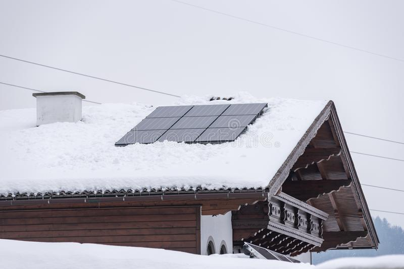 Solar panel, photovoltaic, PV panels on a house with snow covered roof. Electricity from the sun in the mountains. stock image