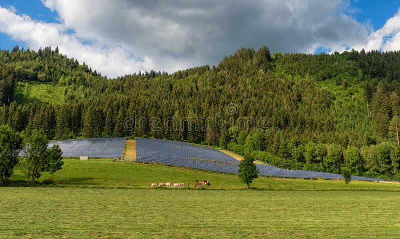 Solar panel power system in a countryside by the forest. Solar panel power system constructed in a farmland by the forest in Austria stock images