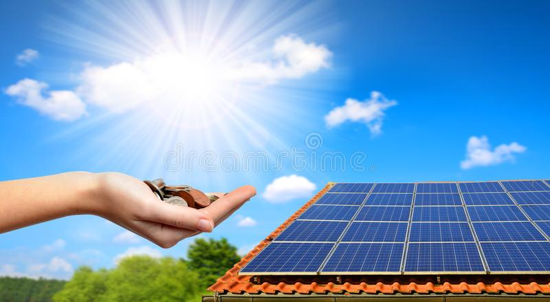Solar panel on the roof of the house and coins in hand. The concept of money saving and clean energy royalty free stock photography