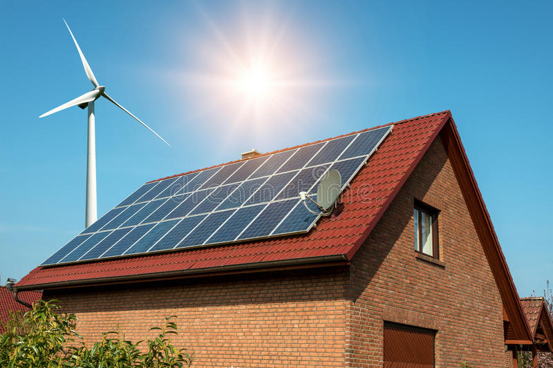 Solar panel on a roof of a house and wind turbins arround. Concept of sustainable resources royalty free stock photos