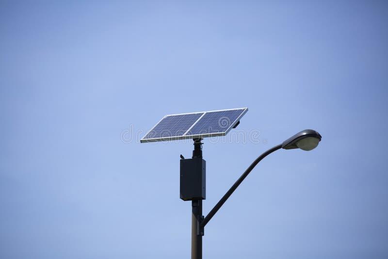 Solar Panel Against Blue Sky. Solar panel on top of a street light stock photo