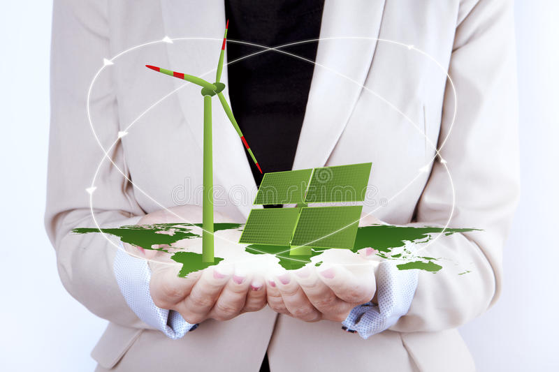 Solar Panel and Wind Turbine in women's hands. Green Energy - Digital symbol of Solar Panel and Wind Turbine on map of earth. All together in woman's hands royalty free stock photography