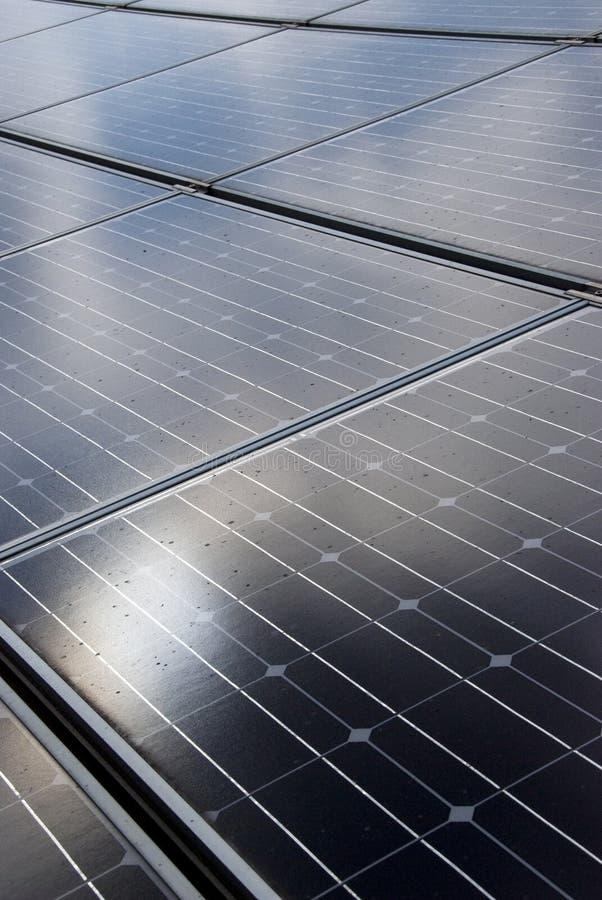 Solar panels. Sun reflecting on roof mounted solar energy panels royalty free stock photography