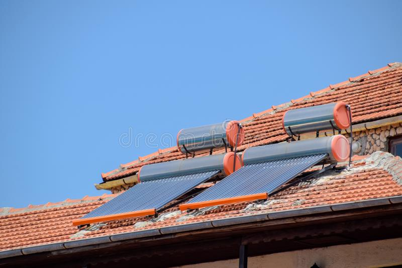 Solar panels and barrels for heating water on roof of the house with clay tiles. Solar panels and barrels for heating water on the roof of the house with clay stock photo