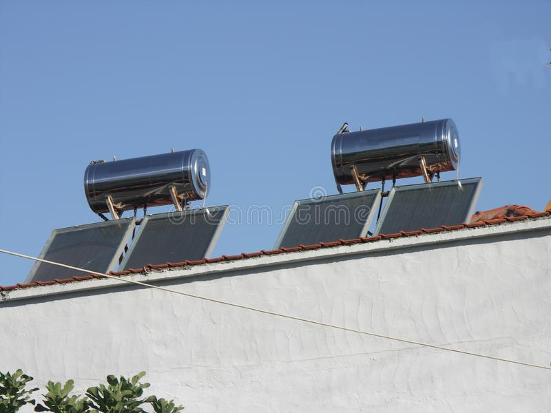 Solar panels and boilers in Stavros, Greece. Solar panels and collectors and boilers on roof of house in Stavros, Greece. Sunny day, clear and blue sky royalty free stock photo