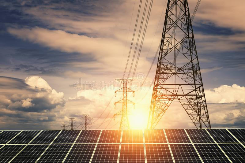Solar panels with electricity pylon and sunset. Clean power energy concept. Transmission, photovoltaic, plant, high, voltage, renewable, green, tower, sky royalty free stock photos