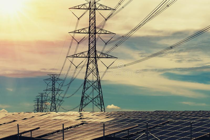 Solar panels with electricity pylon and sunset. Clean power energy concept. Transmission, photovoltaic, plant, high, voltage, renewable, green, tower, sky royalty free stock photo