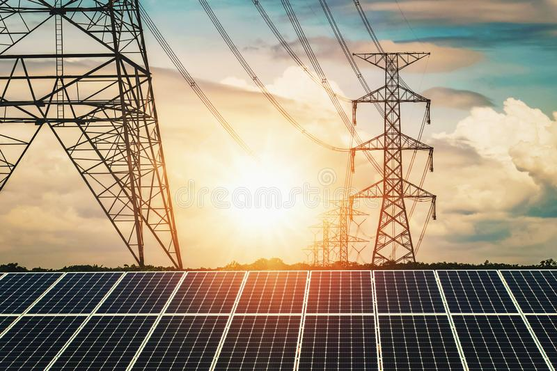 Solar panels with electricity pylon and sunset. Clean power energy concept. Transmission, photovoltaic, plant, high, voltage, renewable, green, tower, sky royalty free stock image