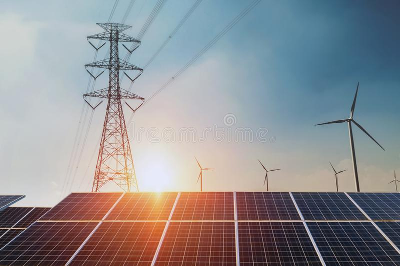 Solar panels with electricity pylon and wind turbine Clean power stock image