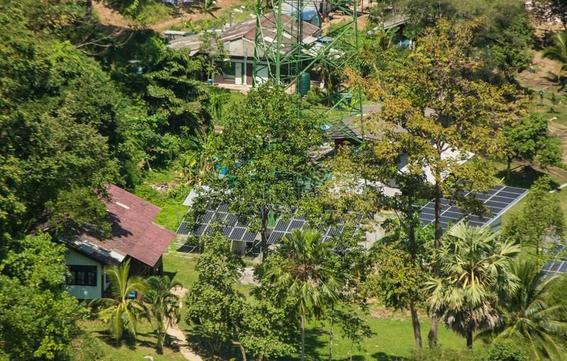 Solar panels in the forest among the palm trees. Alternative solar energy. Large solar panels in the rainforest. Alternative solar energy royalty free stock photography