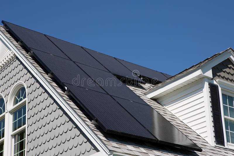Solar Panels on a house. Solar panel installation on a nice cape cod house with sunny blue skies in the background royalty free stock photography