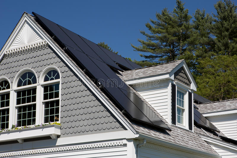Solar Panels on a house. Solar panel installation on a nice cape cod house with sunny blue skies in the background stock photos