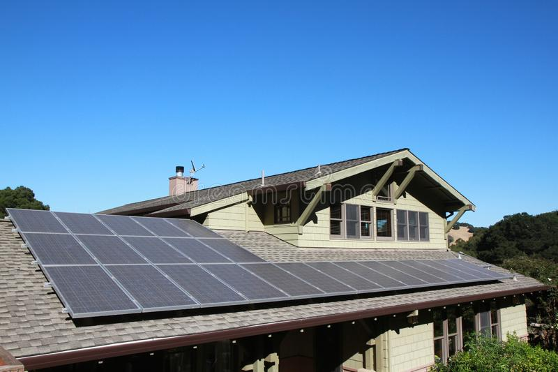Solar panels on roof with copy space. Solar panels on roof of house. horizontal orientation, blue sky, gray panels on brown roof. Ample copy space in blue sky stock photos