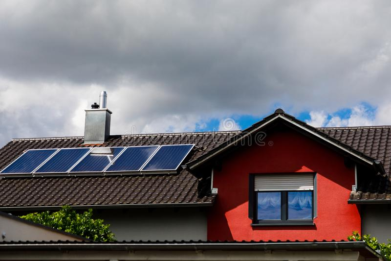 Solar panels on the roof of a house in cloudy weather. The concept of poor location, bad weather, and payback stock photos