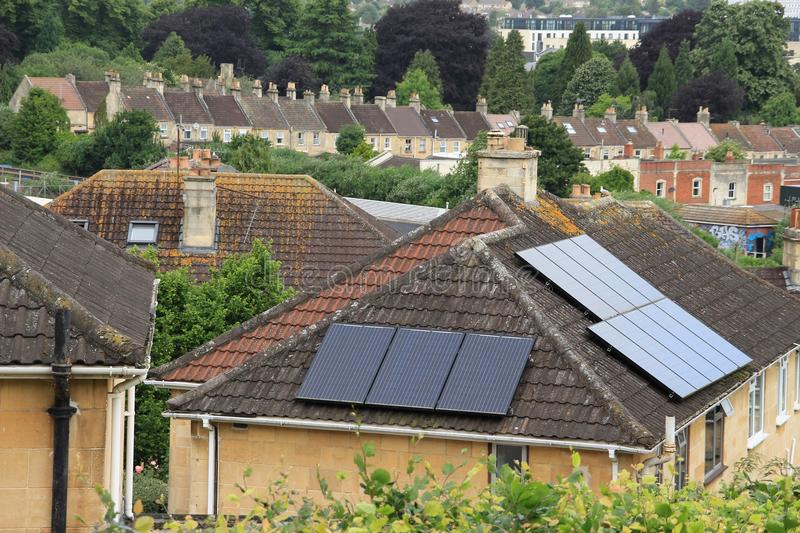 Solar panels and striking chimneys in the city Bath. Solar panels on the roof of the house and in the distance terraced houses with striking chimneys in the stock photography