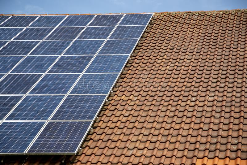 Solar panels on roof of house. horizontal orientation. Blue sky, gray panels on brown roof stock photos