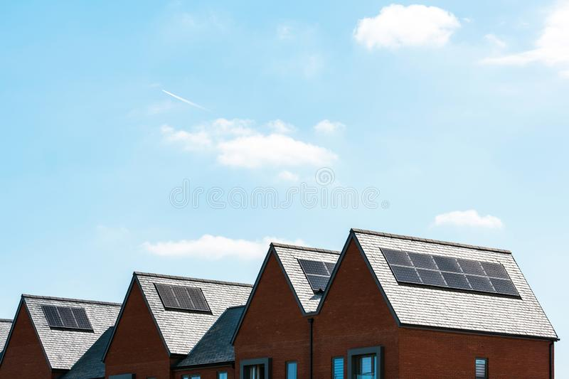 Solar panels on roof of new houses in england uk on bright sunny day.  stock photography