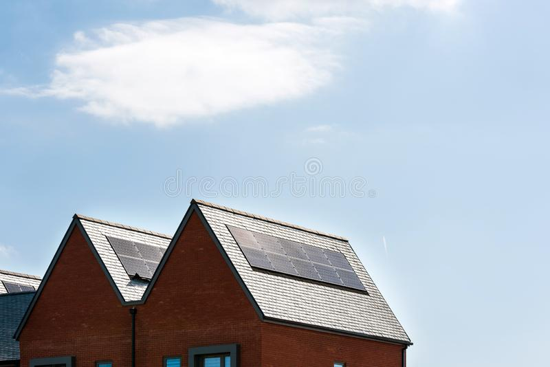 Solar panels on roof of new houses in england uk on bright sunny day.  stock photos