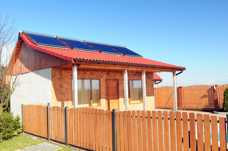 Solar panels on a small house. Bungalow with solar panels on the roof and fragment of wooden fence royalty free stock photo