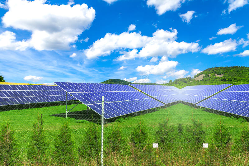 Solar panels with the sunny sky. Green field royalty free stock photography