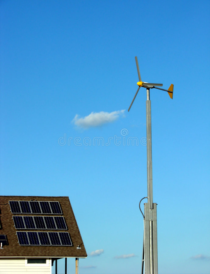 Solar Panels and Wind Turbine Renewable Energy. Wind turbine and solar panels on a roof as renewable energy sources stock image