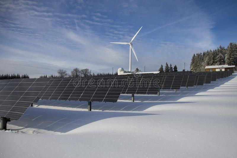 Solar panels and wind turbine in snow